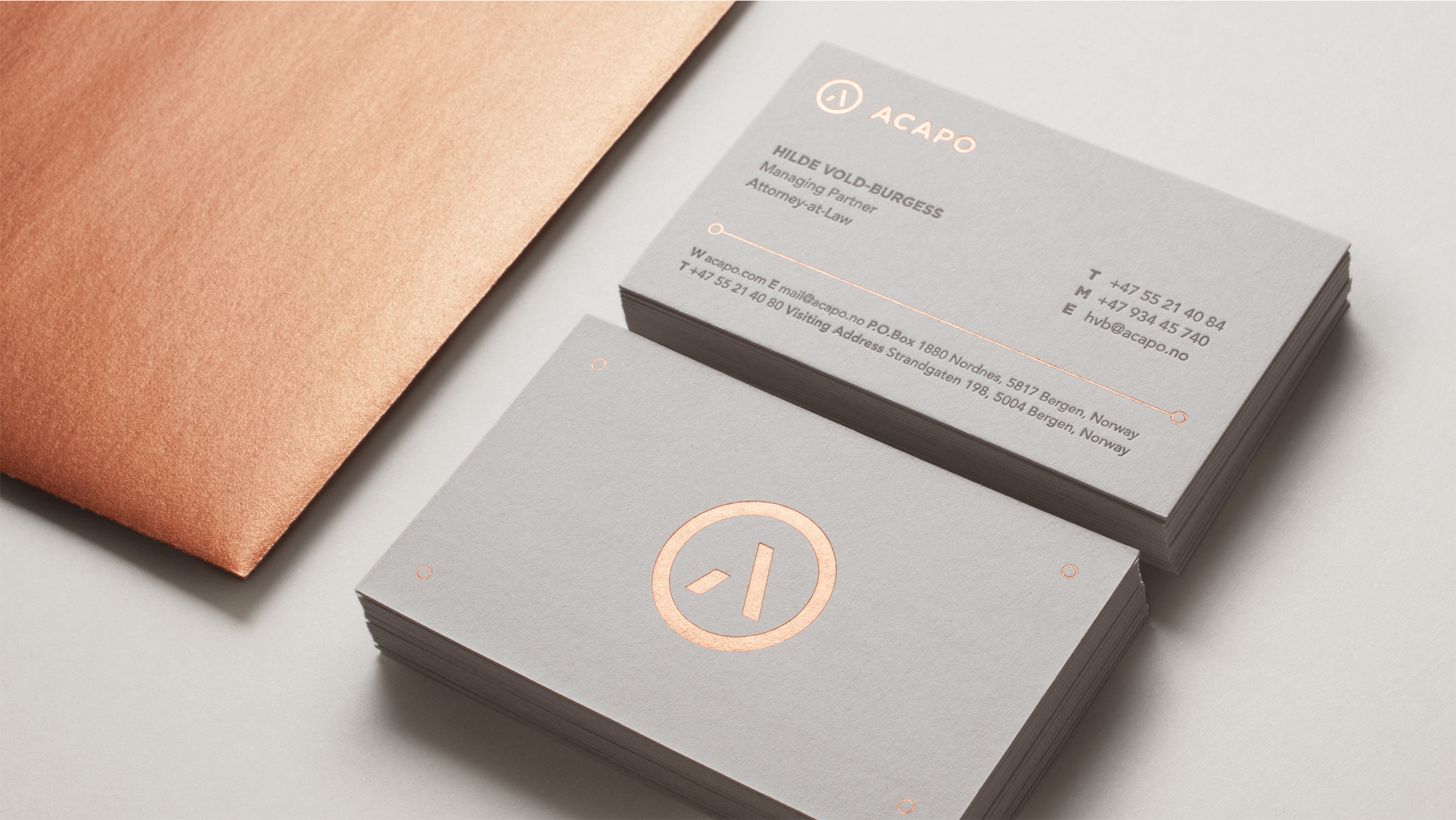 Acapo stationary. Detail photo of business card with copper foil embossing and copper envelope